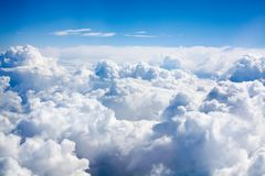 White clouds on blue sky background close up, cumulus clouds high in azure skies, beautiful aerial cloudscape view from above