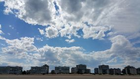 White clouds on the blue sky background over buildings. On the seacoast stock images
