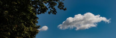 White clouds on a blue sky background on a sunny day. Web banner royalty free stock photo