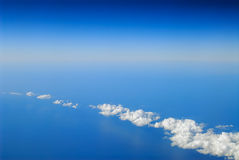 White clouds between blue sky and blue sea Royalty Free Stock Image