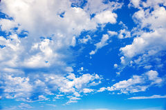 White clouds on a blue sky. Delicate fluffy white clouds in the sunlight against a blue sky. Spring seamless summer. Delicate fluffy white clouds in the sunlight Stock Image