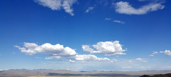 White Clouds in Blue Sky. Over Desert Mountain Landscape near Mountain Pass in California royalty free stock photos