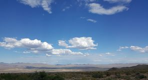 White Clouds in Blue Sky Over Desert Mountain Landscape Stock Images