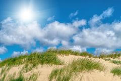 White clouds on blue sky over dunes Stock Photography