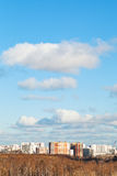 White clouds in blue sky over houses in autumn day Royalty Free Stock Image