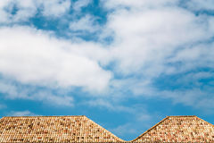 white clouds in blue sky over orange tile roofs Royalty Free Stock Photo
