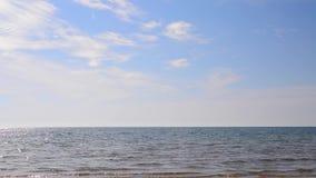 White clouds on a blue sky over the sea. Sandy sea shore. Tropical island. Blue sea water. Seaside resort. Blue sky over the sea. Clouds over the water. Sea stock video footage