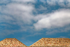 White clouds in blue sky over tile roofs Stock Photography