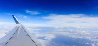 White clouds on a blue sky from a plane window background. Space for text. Fluffy white clouds on a blue sky from a plane window background. Space for text Royalty Free Stock Images