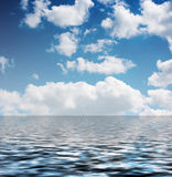 White clouds in the blue sky reflected in the water. On summer day Royalty Free Stock Images