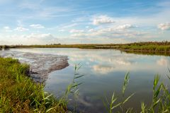 White clouds and a blue sky reflecting in the mirror smooth wate. White clouds and a blue sky reflecting in the smooth water surface of a wide creek in the Dutch stock photography
