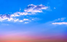 White clouds on blue sky at sunset. Sun at horizon royalty free stock photos