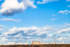 White clouds in blue spring sky over city Stock Photo