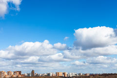 White clouds in blue spring sky over city Stock Image