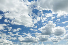 White clouds in blue sunny sky with sun backlight Royalty Free Stock Photos