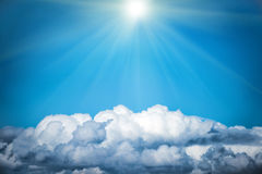 White clouds and bright sun on the blue sky. Nature background Royalty Free Stock Photography