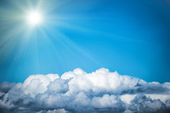 White clouds and bright sun on the blue sky Stock Photo