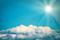 White clouds and bright sun on the blue sky. Nature background, instagram colorized Royalty Free Stock Photo
