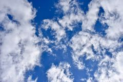 White clouds almost covering the blue sky stock image