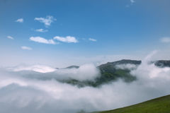 White clouds covering the mountains and the green of the grass field blue sky Stock Image
