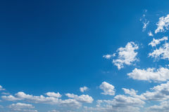 White clouds float through dark blue african sky Royalty Free Stock Photography