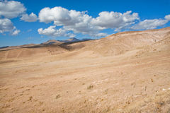 White clouds float over the arid landscape in a valley Stock Photo