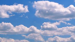 White clouds fly across a bright blue sky. Summer blue sky. Timelapse.