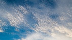 White clouds flying on blue sky. Timelapse stock footage