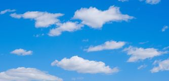 White clouds in a free idyllic blue sky on a Sunny summer day.  stock photo