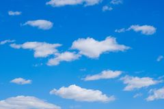 White clouds in a free idyllic blue sky on a Sunny summer day royalty free stock photos