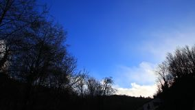White clouds moving slowly in a blue sky with shady trees. In Pyrenees, France stock video