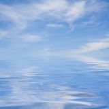 White clouds over a blue ocean Stock Images