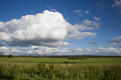 White clouds over the field. White clouds against the blue sky above the green field Royalty Free Stock Image