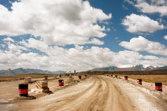 White clouds over the road split by metal barrels to goldmine Royalty Free Stock Images