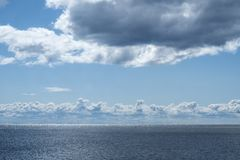 White Clouds Over the Shimmering Sea royalty free stock image