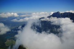 White clouds over Slovenian mount Mangrt. White clouds over Slovenian mountain Mangrt. View of the peaks and the valley beneath from above Royalty Free Stock Image