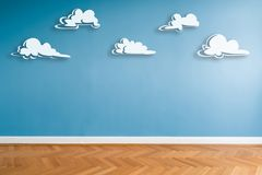 White clouds painted on blue wall in empty room with parquet floor and copy space.  royalty free illustration