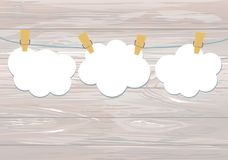 White clouds of paper hang on a rope with clothespins on the woo. Den background. Vector. Free space for text or advertising Royalty Free Stock Image