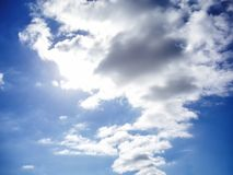 White clouds and a ray of sunshine royalty free stock photography
