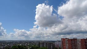 White clouds running over city, bright blue sky. Timelaps. stock video footage