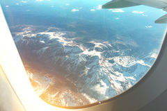 White Clouds Sky and Mountains as Seen Through Window of an Aircraft. Stock Photography