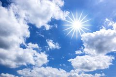 White Clouds and Star-shaped Sun in Blue Sky for Background. Image of scattered puffy white clouds and star-shaped sun in the blue sky background stock images