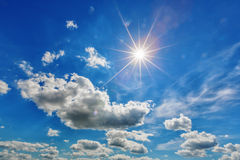 White clouds with sun in blue sky Stock Photos