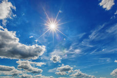 White clouds with sun in blue sky Stock Image