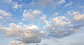 White clouds in sunny blue sky above the sport field with lamp p. Ost background Stock Image
