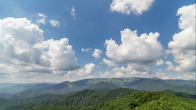 White clouds towering over blue sky and green forest landscape time lapse. Timelapse video of white cumulus clouds towering over blue sky and green mountains and stock video