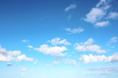 White clouds of various shapes against the blue sky and the sun above the surface of the ocean. stock photography