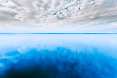 White Cloudscape Over Blue Water Surface Of Lake Pond River. Nat Stock Photos
