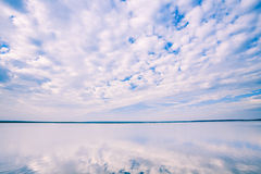 White Cloudscape Over Water Surface Of Lake Pond River Royalty Free Stock Image