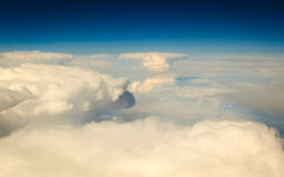 White cloudy sky. View from airplane flying in clouds. Blue white cloudy sky. View from window of airplane flying in clouds. Skyscape cloudscape. Bird's eye Royalty Free Stock Photo